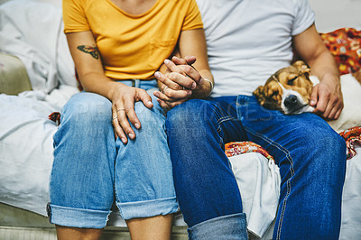 Buy stock photo Cropped shot of a happy young couple relaxing on the sofa with their dog at home