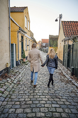 Buy stock photo Rearview shot of a happy young couple traveling and walking together outdoors in a foreign town