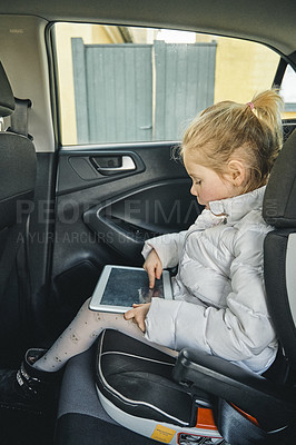 Buy stock photo Shot of an adorable little girl using a digital tablet while traveling in the backseat of a car