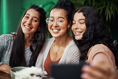 Buy stock photo Shot of young sisters taking selfies together at a cafe