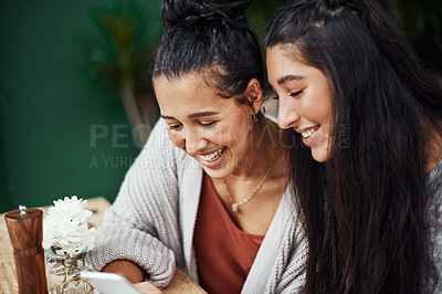 Buy stock photo Shot of young sisters using a smartphone together at a cafe