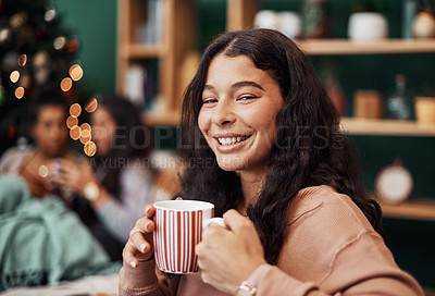 Buy stock photo Shot of a beautiful young woman enjoying a warm beverage with her friends in the background during Christmas at home