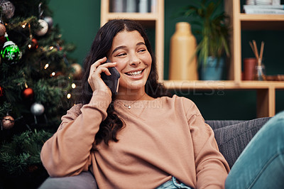 Buy stock photo Shot of a beautiful young woman using a smartphone on the sofa during Christmas at home