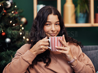 Buy stock photo Shot of a beautiful young woman enjoying a warm beverage on the sofa during Christmas at home