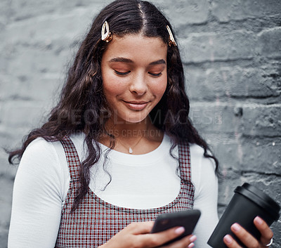 Buy stock photo Cropped shot of an attractive teenage girl standing alone and using her cellphone while holding a cup of coffee