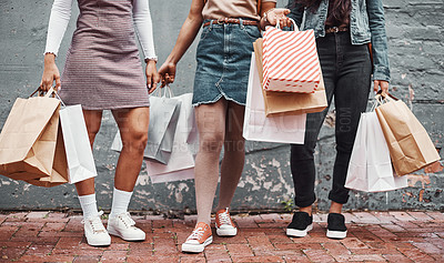Buy stock photo Cropped shot of an unrecognizable group of sisters standing together with their shopping bags during a day in the city