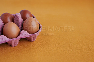 Buy stock photo Studio shot of chicken eggs in a carton against a colored  background