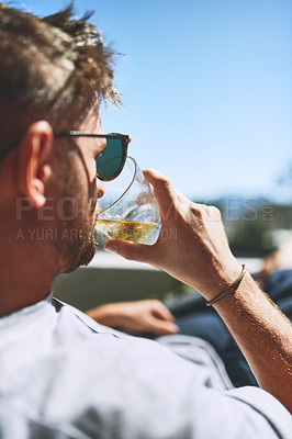 Buy stock photo Cropped shot of a relaxed young man having a drink while looking at the view from his balcony outside at home during the day