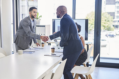 Buy stock photo Shot of two businessmen shaking hands together during their meeting inside a boardroom