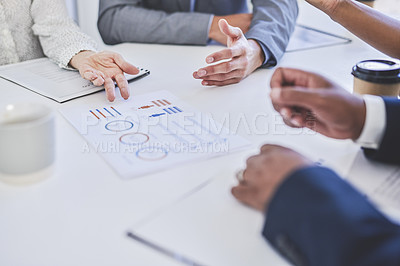 Buy stock photo Cropped shot of a group of unrecognizable businesspeople planning and going over paperwork during their meeting in a boardroom