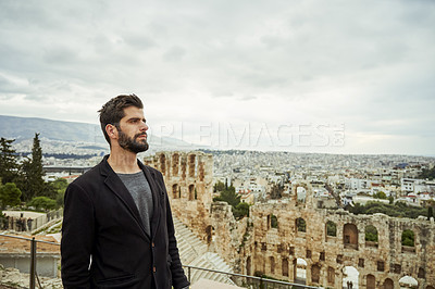 Buy stock photo Cropped shot of a handsome young man standing alone near the Odeon of Herodes Atticus while sight-seeing in Greece