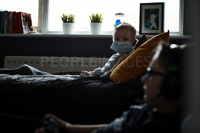 Buy stock photo Shot of an adorable little boy wearing a surgical mask and lying down on the sofa at home
