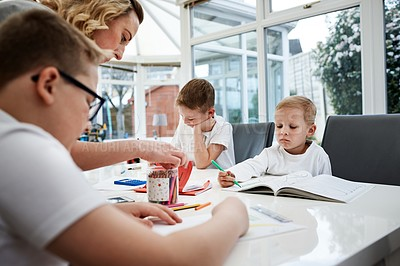 Buy stock photo Cropped shot of a mother helping her young sons with their homework at home