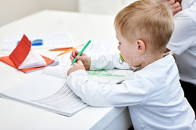 Buy stock photo Cropped shot of an adorable little boy busy drawing on a notepad at home