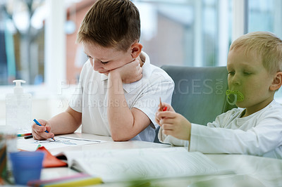 Buy stock photo Cropped shot of two adorable little boys drawing and doing their schoolwork together at home