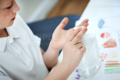 Buy stock photo Cropped shot of an adorable little boy sanitizing his hands before doing his homework at home