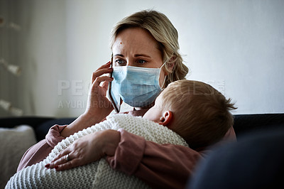 Buy stock photo Shot of a mother wearing a surgical mask making a phone call while taking care of her young son at home