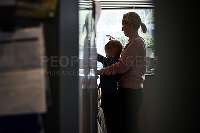 Buy stock photo Shot of a young mother using her cellphone while preparing a meal with her young son at home