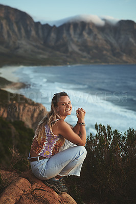 Buy stock photo Full length portrait of an attractive young woman crouched on the mountainside near the sea alone during a day outdoors