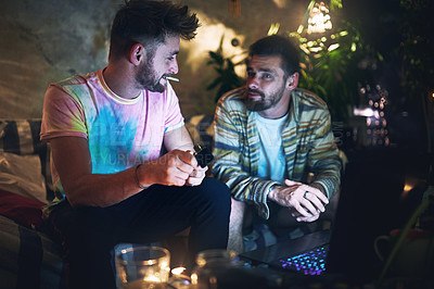 Buy stock photo Cropped shot of a handsome young man lighting up a joint of cannabis while sitting with is friend at home