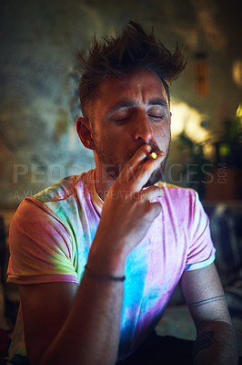 Buy stock photo Cropped shot of a handsome young man smoking a blunt of cannabis while sitting alone at home