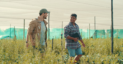 Buy stock photo Cropped shot of two handsome young male farmers working together in a crop field during the day
