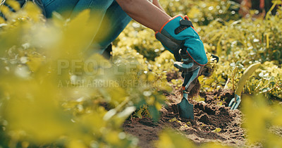 Buy stock photo Cropped shot of an unrecognizable female farmer planting crops in a field during the day