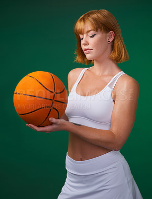 Buy stock photo Cropped shot of an attractive young sportswoman standing alone and holding a basketball against a green background in the studio