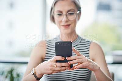 Buy stock photo Cropped shot of a mature businesswoman using her cellphone in her office