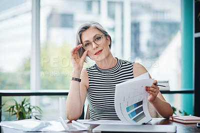 Buy stock photo Shot of of a mature businesswoman working on paperwork in her office`