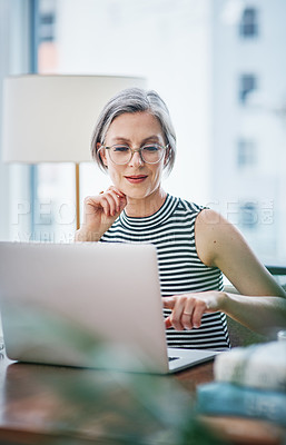 Buy stock photo Shot of a mature businesswoman using her laptop while sitting at her desk