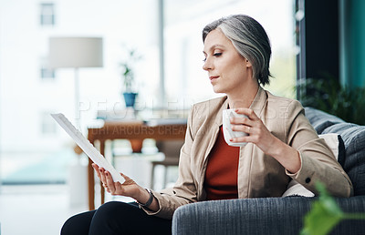 Buy stock photo Cropped shot of an attractive mature businesswoman sitting alone and enjoying a cup of coffee while reading paperwork