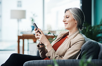 Buy stock photo Cropped shot of an attractive mature businesswoman sitting alone and using a cellphone in her home office