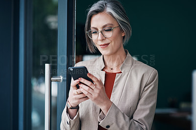 Buy stock photo Cropped shot of an attractive mature businesswoman standing alone and using her cellphone in her home office