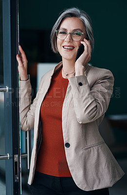 Buy stock photo Cropped portrait of an attractive mature businesswoman standing alone and talking on her cellphone in her home office