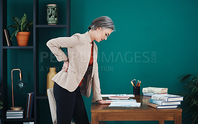 Buy stock photo Cropped shot of an attractive mature businesswoman standing and suffering from backache while in her home office