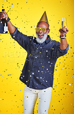 Buy stock photo Portrait of a cheerful senior man celebrating and drinking champagne in studio against a yellow background