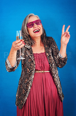 Buy stock photo Portrait of a funky and cheerful senior woman drinking a glass of champagne in studio