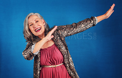 Buy stock photo Portrait of a funky and cheerful senior woman dancing in studio against a blue background