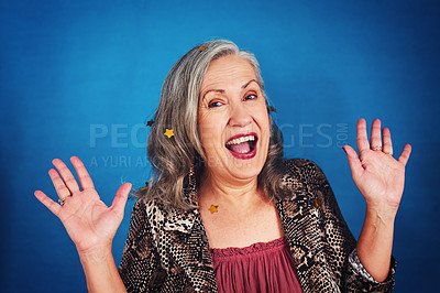 Buy stock photo Portrait of a funky and stylish senior woman posing in studio against a blue background