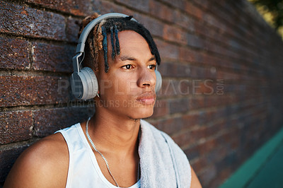 Buy stock photo Shot of a sporty young man listening to music outdoors