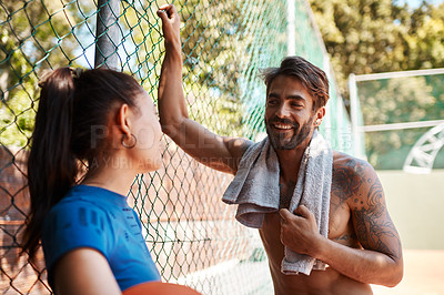 Buy stock photo Shot of two sporty young people chatting to each other against a fence on a sports court