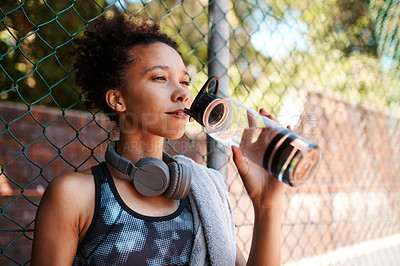 Buy stock photo Shot of a sporty young woman drinking water while standing against a fence outdoors