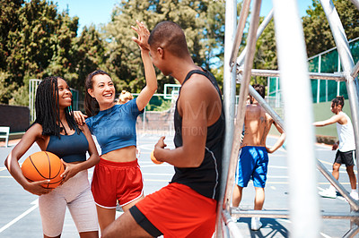 Buy stock photo Shot of a sporty young woman giving her teammate a high five on a basketball court