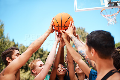 Buy stock photo Shot of a group of sporty young people standing together in a huddle around a basketball on a sports court