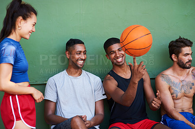Buy stock photo Shot of a group of sporty young people taking a break after a game of basketball