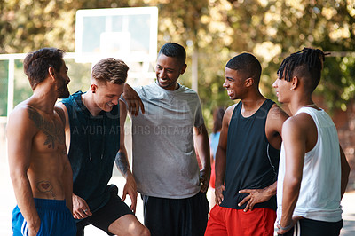 Buy stock photo Shot of a group of sporty young men standing on a basketball court