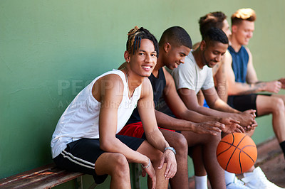 Buy stock photo Portrait of a sporty young man taking a break with his friends after a game of basketball