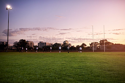 Buy stock photo Full length shot of a diverse group of sportsmen playing rugby at dusk in a sports club
