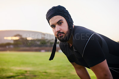 Buy stock photo Cropped portrait of a handsome young sportsman wearing headgear and crouching alone during rugby practice during the day